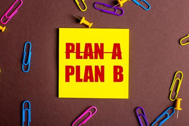 Die wörter plan b sind rot auf einem gelben aufkleber auf einer braunen oberfläche neben mehrfarbigen büroklammern geschrieben