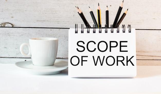 Die wörter scope of work sind in einem weißen notizblock neben einer weißen tasse kaffee auf einer hellen oberfläche geschrieben