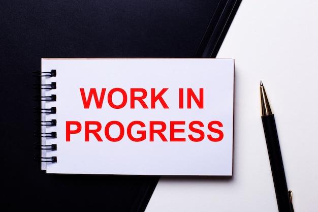 Die wörter work in progress sind rot auf einer schwarz-weißen oberfläche in der nähe des stifts geschrieben