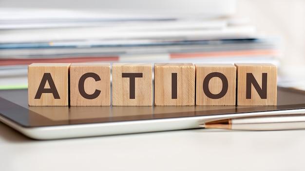 Die wortaktion auf holzwürfeln geschrieben, im hintergrund ein stapel von dokumenten, selektiver fokus. kann für business, bildung, finanzen, marketingkonzept verwendet werden.