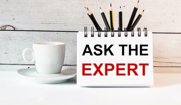 Die worte ask the expert stehen in einem weißen notizblock neben einer weißen tasse kaffee auf einer hellen oberfläche