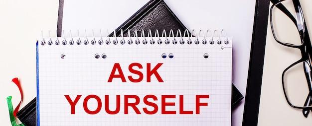 Die worte ask yourself sind in einem weißen notizbuch neben einer schwarz gerahmten brille rot geschrieben