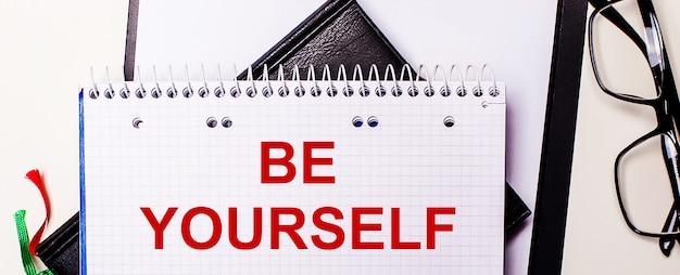 Die worte be yourself sind in einem weißen notizbuch neben einer schwarz gerahmten brille rot geschrieben