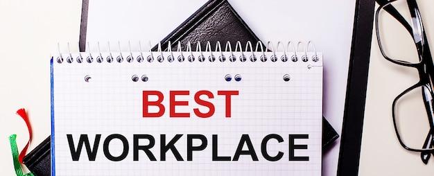 Die worte best workplace sind in einem weißen notizbuch neben einer schwarz gerahmten brille rot geschrieben