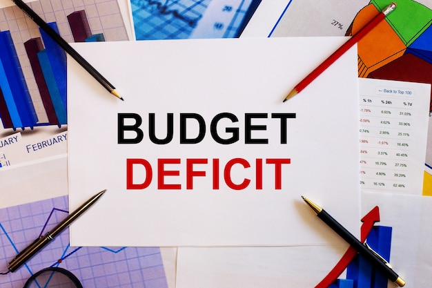 Die worte budget deficit stehen auf einer weißen fläche in der nähe von farbigen grafiken, kugelschreibern und bleistiften. geschäftskonzept