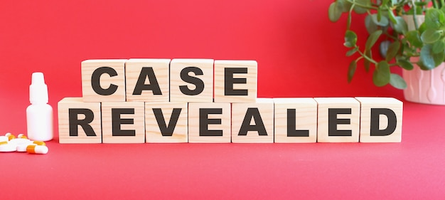 Die worte case revealed bestehen aus holzwürfeln auf rotem grund mit medikamenten.