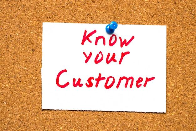 Die worte know your customer auf einer notizkarte, die an einer pinnwand aus kork befestigt ist, um daran zu erinnern, ihren geschäftsmarkt zu erforschen