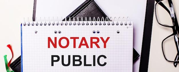 Die worte notary public sind in einem weißen notizbuch neben einer schwarz gerahmten brille rot geschrieben