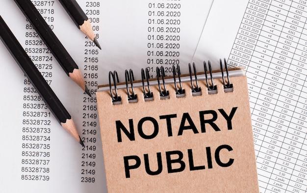 Die worte notary public stehen auf dem braunen notizbuch. in der nähe stifte