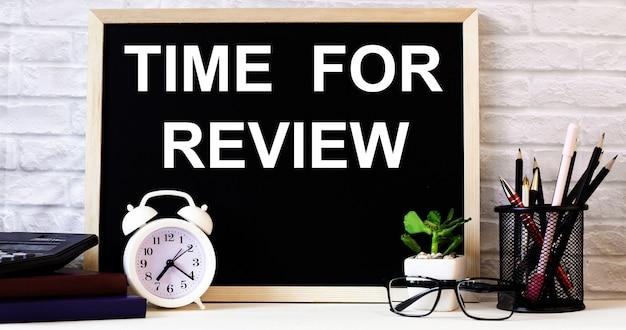 Die worte time for review stehen an der tafel neben dem weißen wecker, den gläsern, der topfpflanze und den stiften in einem ständer