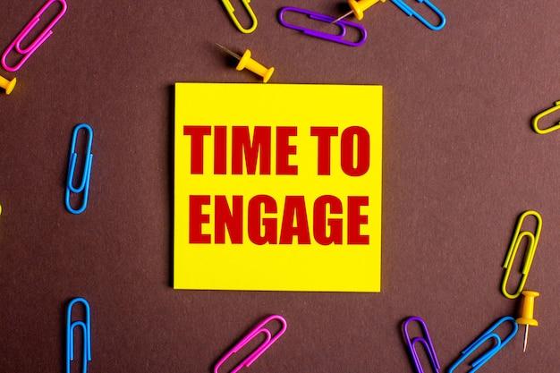 Die worte time to engage sind rot auf einem gelben aufkleber auf einer braunen oberfläche neben mehrfarbigen büroklammern geschrieben