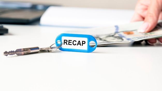 Die wortzusammenfassung wird auf ein blaues keychain geschrieben. der schlüssel liegt auf dem schreibtisch. im hintergrund hält eine frauenhand geldscheine