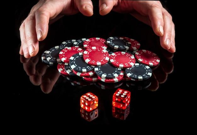 Die würfel mit der maximalen gewinnkombination von zwölf beim craps auf dem schwarzen tisch und die hände nehmen die chips vom gewinn