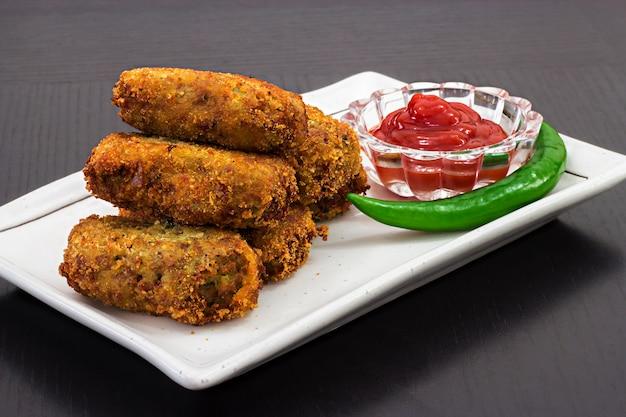 Die würzigen goldenen gebratenen klaren koteletts, die tomatensauce oder ketschup auf weißer platte gedient werden, bereiten sich für iftar ramadan vor. tiefenschärfe