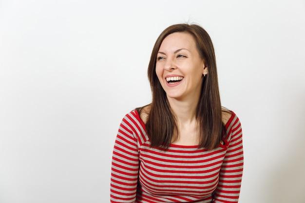 Die wunderschöne europäische junge glückliche braunhaarige frau mit gesunder, sauberer haut und charmantem lächeln, gekleidet in lässige rote und graue kleidung, lacht und genießt auf weißem hintergrund. emotionen-konzept.