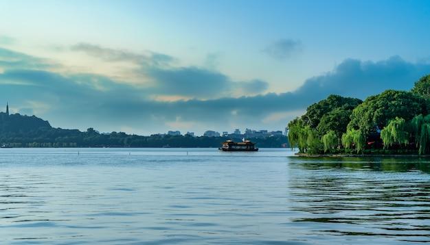 Die wunderschöne naturlandschaft und die holzboote des hangzhou west lake
