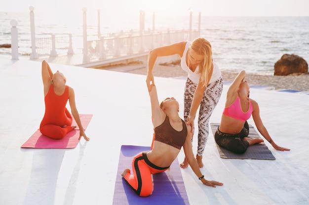 Die yogalehrerin zeigt den mädchen, wie man die pose richtig macht