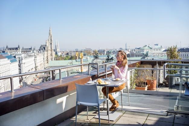 Die youngwoman, die frühstückt, diente in einem dach des europäischen stadtgebäudes