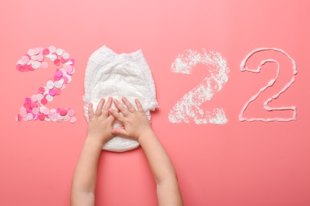 Die zahlen 2022 sind mit konfetti, windel, talkumpuder und babycreme auf pinkfarbenem grund ausgekleidet. themenorientierte weihnachtskarte für den feiertag. neujahr und weihnachten.