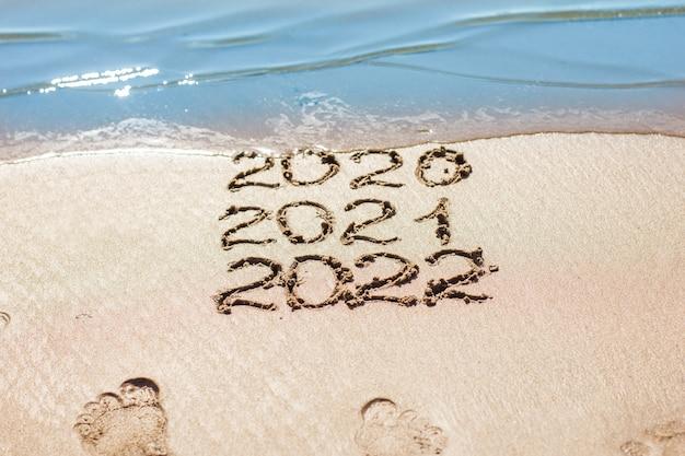 Die zahlen werden auf den sand gezeichnet und von der welle weggespült das symbol des neuen jahres die veränderung