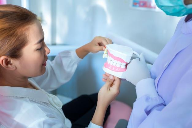 Die zahnärztin zeigt, wie man den patienten auf dem zahnarztstuhl in ihrer klinik zähne putzt.