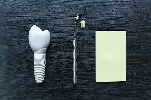 Die zahnprothese ruht auf einem schwarzen holztisch. zahnprothese.