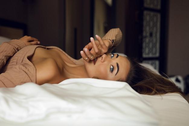 Die zarte junge blondine liegt auf dem bett im hotelzimmer, ist einsam und wartet auf den mann ihres lebens. schlanke finger in der nähe der lippen, blaue augen schauen in das fenster. nude stilvolles make-up und haare.
