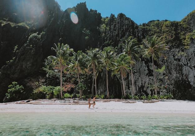 Die zeit am strand genießen. menschen, die auf dem weißen sand mit tropischem dschungel gehen. konzept über reisen und natur