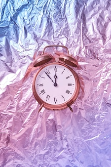 Die zeit ist um fünf minuten vor mitternacht auf einem gemalten goldenen retro-wecker vor dem abstrakten glänzenden rosa-blauen hintergrund. grußkarte.