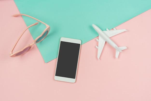Die zubehörartikel der frauen mit intelligentem telefon auf pastellfarbhintergrund, sommerferienkonzept