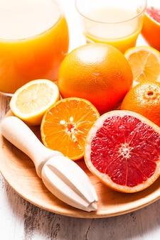 Die zubereitung für zitrussaft zum frühstück. zitrusreibe aus holz mit früchten.