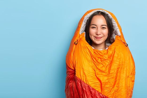 Die zufriedene junge brünette asain-frau, die in einen warmen orangefarbenen schlafsack gewickelt ist, verbringt ihre freizeit aktiv, ist ein aktiver camper und steht an der blauen wand