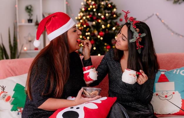 Die zufriedene tochter füttert ihre mutter mit einem keks, der auf der couch sitzt und die weihnachtszeit zu hause genießt
