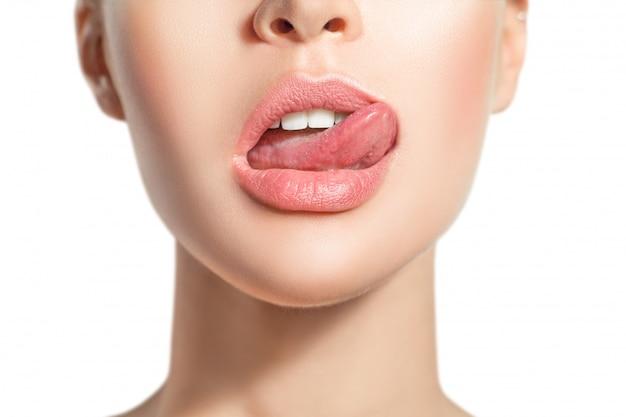 Die zunge der frau leckt verführerisch die lippen.