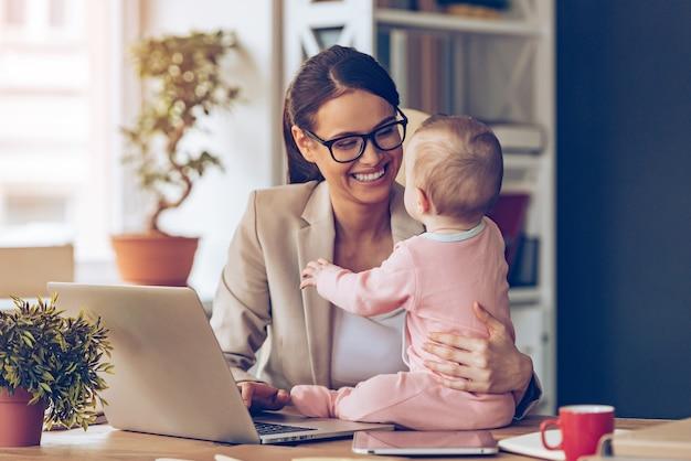 Die zusammenarbeit macht so viel spaß! fröhliche junge schöne geschäftsfrau, die ihr baby mit einem lächeln betrachtet, während sie an ihrem arbeitsplatz sitzt