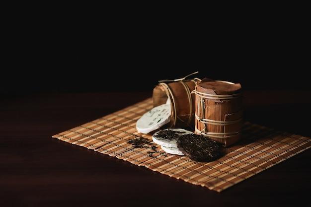 Die zusammensetzung des verpackten chinesischen puer tees auf einer bambusmatte.