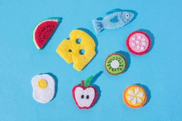 Die zusammensetzung von kunsthandwerk aus filz in form von lebensmitteln und früchten. hobbys und buntes kunsthandwerk. von oben betrachten.