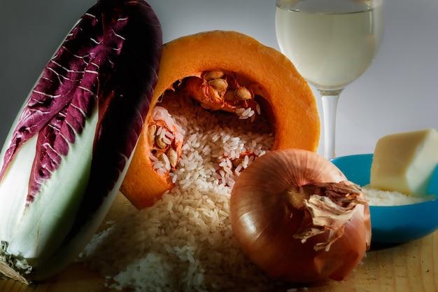 Die zutaten des radicchio-kürbis-risottos. reis, radicchio, kürbis, zwiebel, weißwein, parmesan, butter und gemüsebrühe.