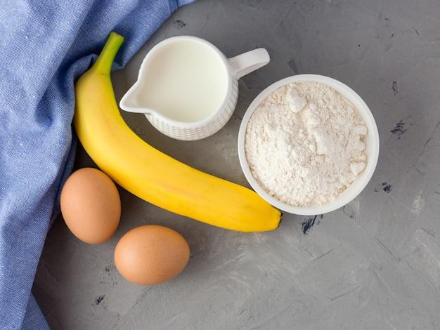 Die zutaten für den bananenkuchen auf grauer oberfläche. holzlöffel, banane, eier, milch