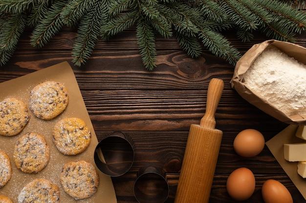 Die zutaten für die herstellung von weihnachtsplätzchen liegen auf einem holztisch