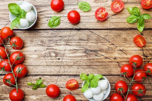 Die zutaten für einen caprese-salat. basilikum, mozzarellabälle und tomaten mit kopienraum.