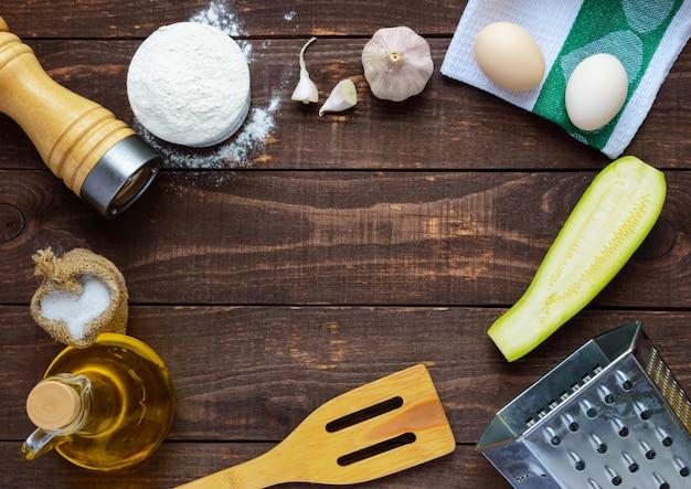 Die zutaten und werkzeuge zum kochen von pfannkuchen aus zucchini auf einem dunklen holztisch. draufsicht. in der mitte des freien platzes für text