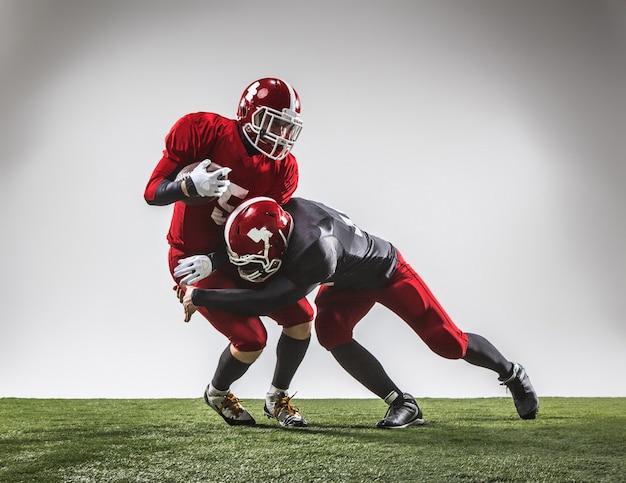 Die zwei american-football-spieler in aktion auf grünem gras und grauem hintergrund.