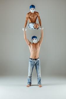 Die zwei gymnastischen akrobatischen kaukasischen männer im gleichgewicht posieren