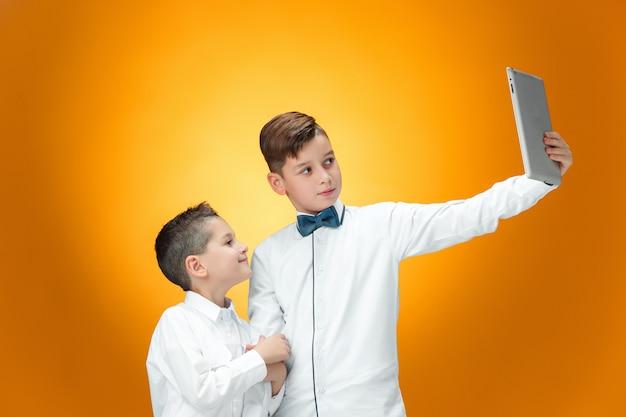 Die zwei jungen, die laptop auf orange hintergrund verwenden