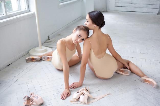 Die zwei klassischen balletttänzer posieren auf weißem holzboden