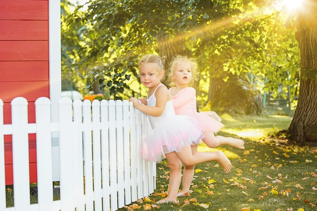 Die zwei kleinen mädchen am spielplatz gegen park oder grünen wald