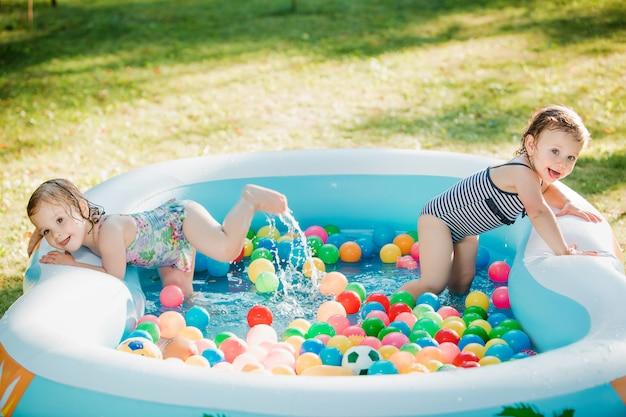 Die zwei kleinen mädchen spielen mit spielzeug im aufblasbaren pool am sonnigen sommertag