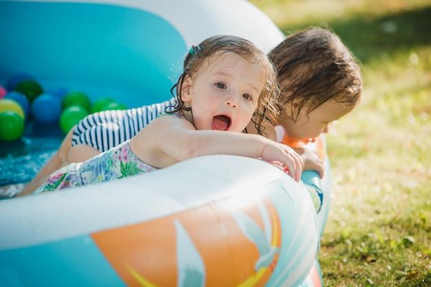Die zwei kleinen mädchen spielen mit spielzeug im aufblasbaren pool im sonnigen sommertag
