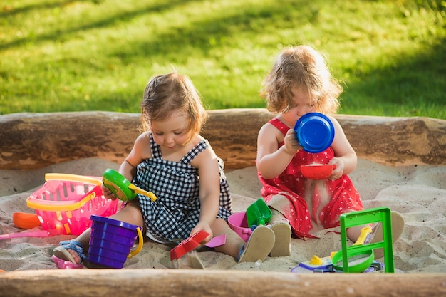 Die zwei kleinen mädchen spielen spielzeug im sand